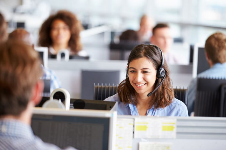Contact center agent smiling talking on headset.