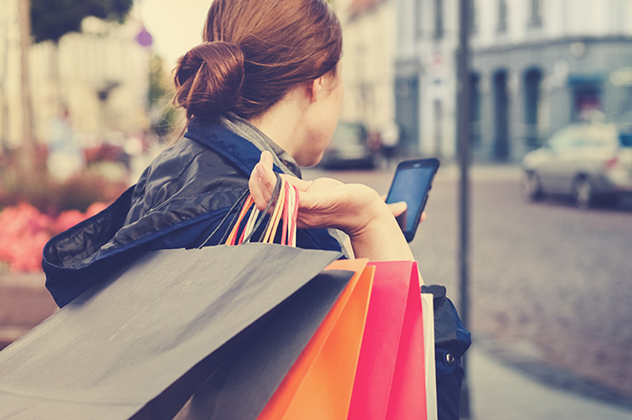 Woman Using Mobile to Browse While Shopping showing omnichannel retail customer experience and omnichannel vs. multi-channel