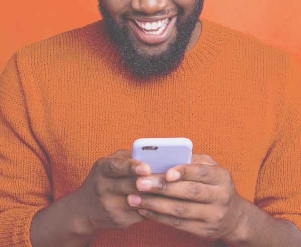 man looking at phone orange background