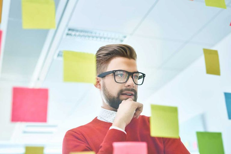 business man with glasses planning customer service management strategy at a board with sticky notes