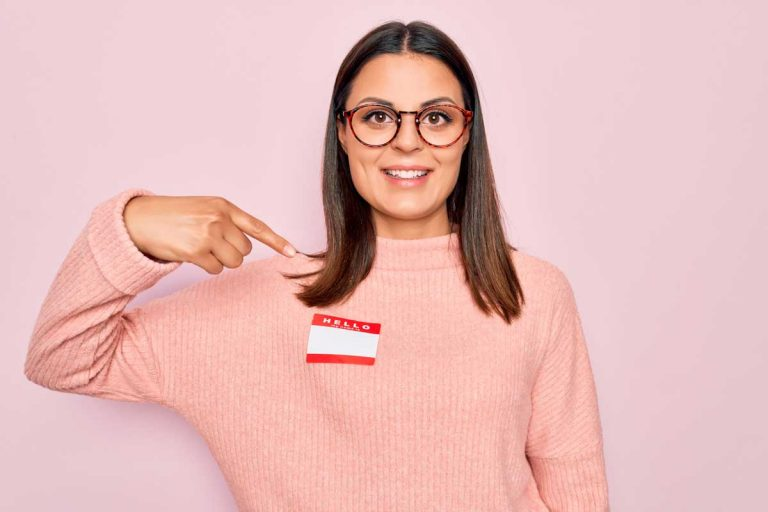 woman pointing to name tag as example of personalized customer experience